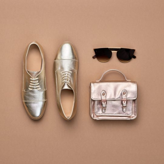 Fall fashion Accessories set. Autumn mood, creative minimal Flat lay. Trendy Sunglasses, Stylish gold loafers shoes, glamour handbag, fashionable look. Autumnal color, shopping concept